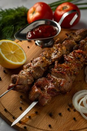 Shashlik on a wooden board with lemon, tomatoes, onions, sauce and parsley