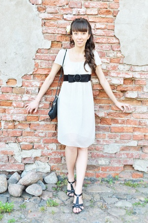 Beautiful young woman with long straight brown hair on brick wall background photo
