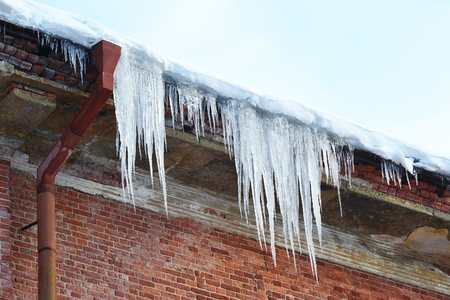 the photo of a icicles drooping from the roof.