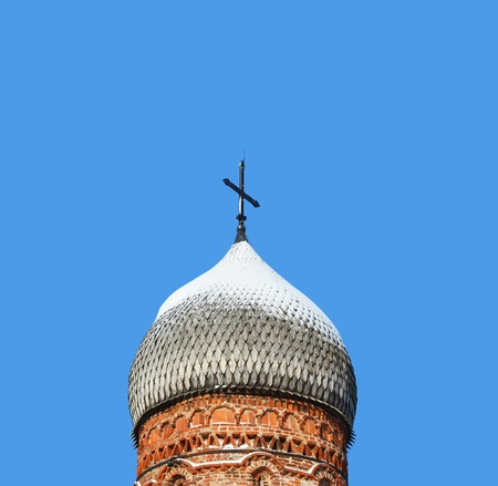 Old wooden dome of church on blue sky background in Novgorod Russia photo
