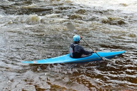 River Vuoksi, Leningrad Region, Russia - 3 July 2011: Kayaker sporting a kayak cuts through water. Stock Photo - 10807893