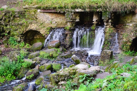 Summer landscape - small waterfall in park, Pavlovsk, surroundings of St. Petersburg, Russia. photo