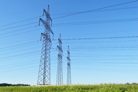 View of electricity pylons against blue sky photo