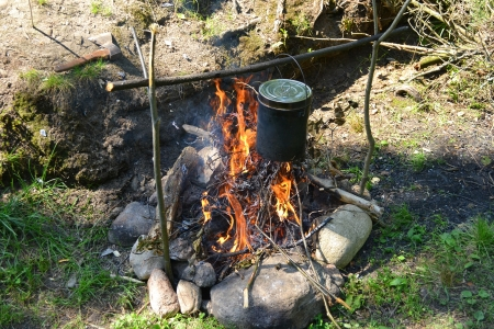 The image of a fire in the woods on which is brewed pot photo