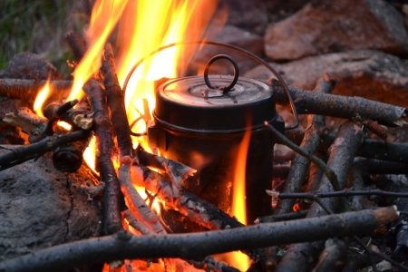 cooking utensils: The image of a fire in the woods on which is brewed pot