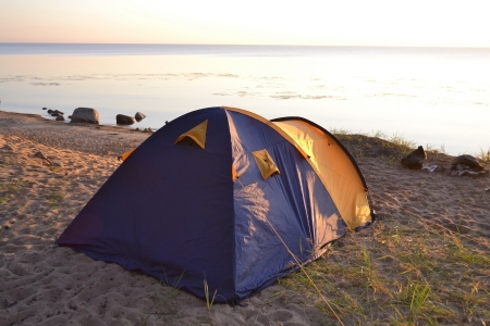 The photo of camping tent on the beach at dawn photo