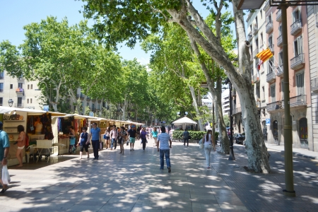 Barcelona, Spain - June 22, 2013:  Tourists walk famous Rambla street in Barcelona.