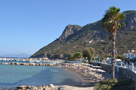 longue: KEFALOS, GREECE - SEPTEMBER 5, 2014: Embankment in Kefalos on a Greek island of Kos. Foreground beach with vacationers people.