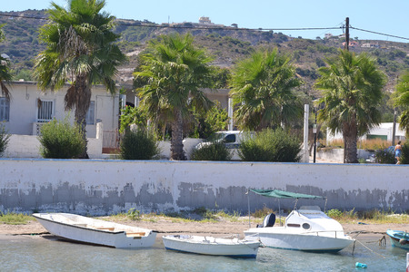 beack: Pleasure boats and embankment of Kefalos, Greece. Stock Photo