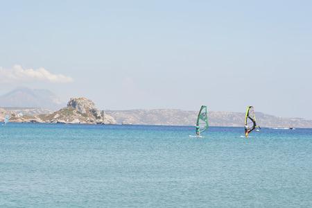 windsurfers: KEFALOS, GREECE - SEPTEMBER 5, 2014: Windsurfers in the Aegean Sea, Greece.