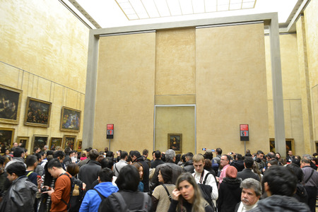 PARIS, FRANCE - JANUARY 6, 2013: Crowd of people looking at a picture of the Mona Lisa in Louvre Museum in Paris.