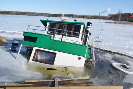 abandonment: LAPPEENRANTA, FINLAND - MARCH 25, 2015: Sunken ship in Lappeenranta harbor on the Saimaa lake at winter, Finland.