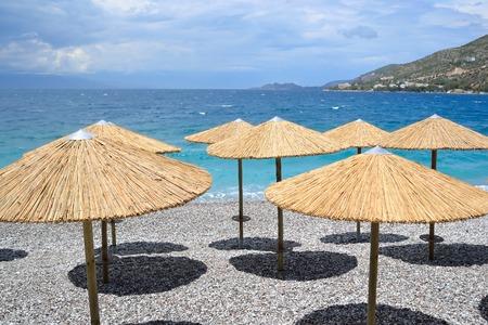 sun umbrellas: Sun umbrellas on the beach in Loutraki, Greece.