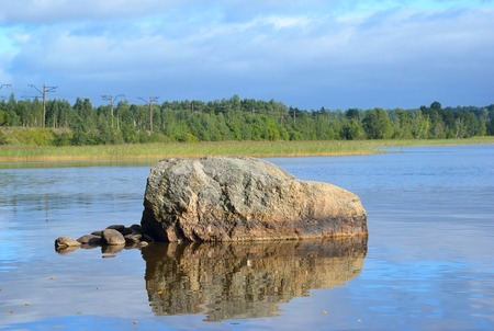isthmus: Lake on a summer day. Huge granite boulder in the foreground. Karelian Isthmus. Stock Photo