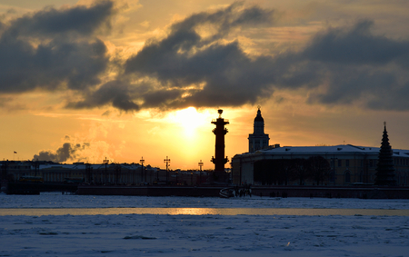 to spit: View of Neva River and Rostral Columns and Spit of Vasilyevsky Island at winter sunset, Russia.