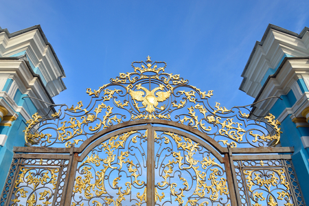 Fragment of Catherine palace fence in Tsarskoye Selo with golden double-headed eagle, suburb of St.Petersburg, Russia.