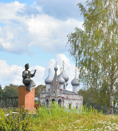 Muse in the image of the Vologda peasant girl with a pipe and Church of St. John Chrysostom with bell tower in Vologda, Russia. Stock Photo