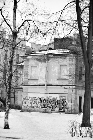 decrepitude: ST.PETERSBURG, RUSSIA - 5 MARCH 2016: Old house with graffiti on Maple Street in historical center of St.Petersburg at winter. Black and white.