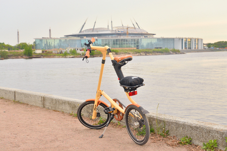 ST.PETERSBURG, RUSSIA - 20 MAY, 2016: Bicycle Strida on coast of river at sunset. On the background new Zenit Stadium.