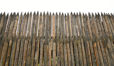 High wooden stockade made of logs at cloud day. Stock Photo
