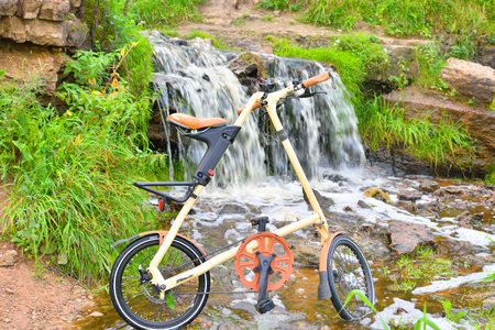 ULYANOVKA, RUSSIA - 26 AUGUST 2016: Bicycle Strida on small waterfall background. Strida - folding bike with a memorable frame in the shape of the letter A. Editorial