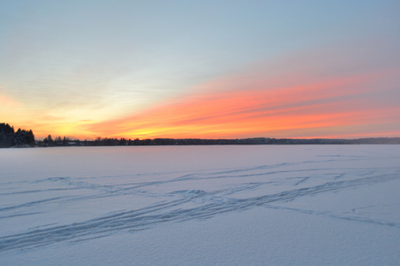 snowscene: Winter landscape at sunset with tracks from cross-country skis.