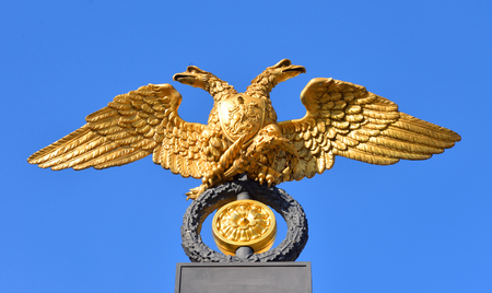 Double-headed eagle - the emblem of the Russian Empire on the gate of the State Russian Museum on blue sky background in St.Petersburg, Russia. Stock Photo