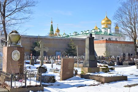april 15: ST.PETERSBURG, RUSSIA - 15 APRIL 2017: Old stone crypt in Novodevichye Cemetery at sunny winter day. The burial covers the period from the 1850s to the present.