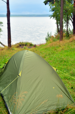 Camping tent in the summer forest on coast of lake.