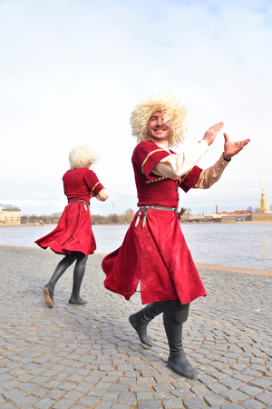 ST.PETERSBURG, RUSSIA - 9 APRIL 2017: Group of people in national Caucasian costumes is dancing lezginka on city street in the center of St. Petersburg.