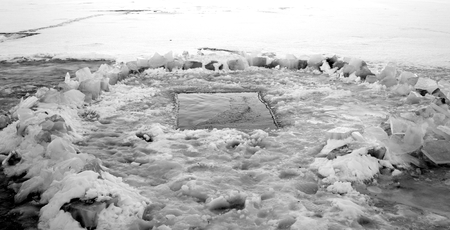 Ice on the river with an ice-hole. Black and white.