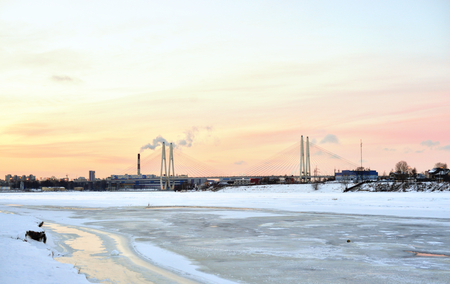 Cable stayed bridge and Neva river on the outskirts of St. Petersburg at winter sunset, Russia.