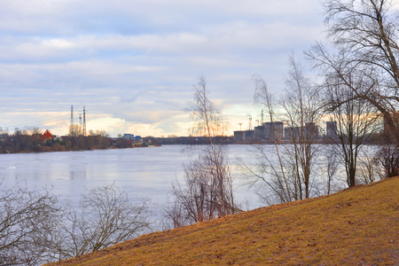Early spring park on coast of Neva River at cloud day, Russia. Stock Photo