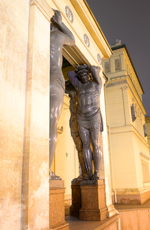 Building of New Hermitage with statues of Atlanteans in center of St.Petersburg at night, Russia. Фото со стока