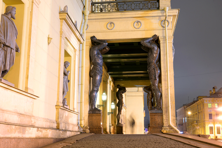Building of New Hermitage with statues of Atlanteans in center of St.Petersburg at night, Russia. Редакционное