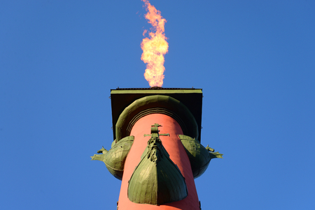 Rostral column with a fiery torch on blue sky background in Saint Petersburg, Russia. 免版税图像