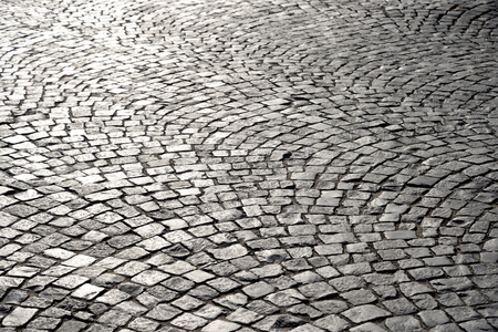 Cobblestone sidewalk made of small stones at sunny day.