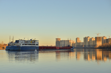 Cargo ship on the Neva river at autumn sunset, outskirts of St.Petersburg, Russia.