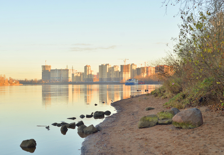 Coast of Neva River and modern residential buildings under construction on the outskirts of St. Petersburg at sunny autumn evening, Russia.