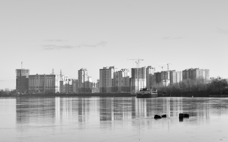 View of Neva River and modern residential buildings under construction on the outskirts of St. Petersburg, Russia. Black and white.
