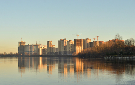 View of Neva River and modern residential buildings under construction on the outskirts of St. Petersburg at sunny autumn evening, Russia.