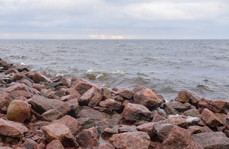 Granite rocks on coast of Gulf of Finland of Baltic Sea at cloud day, Russia.