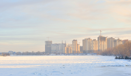View of Neva River and modern residential buildings under construction on the outskirts of St. Petersburg, Russia.