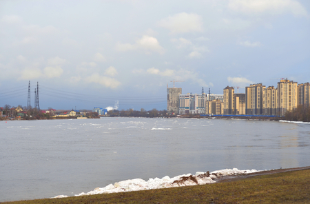 View of Neva River and modern residential buildings under construction on the outskirts of St. Petersburg at cloud spring day, Russia.