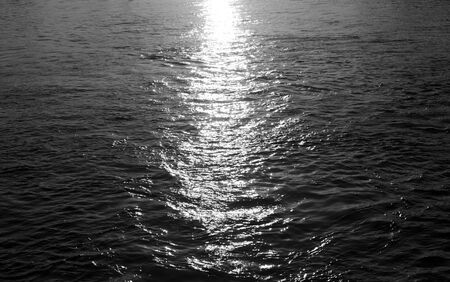 Water with reflection of the sun. Black and white.