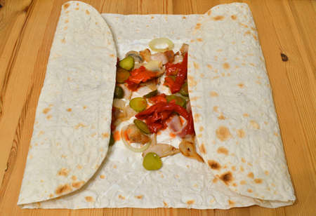 Homemade shawarma in thin wheat tortilla in the process of cooking.