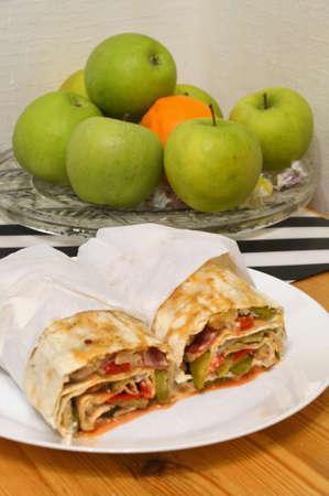 Homemade shawarma in thin wheat tortilla in white plate. Foto de archivo
