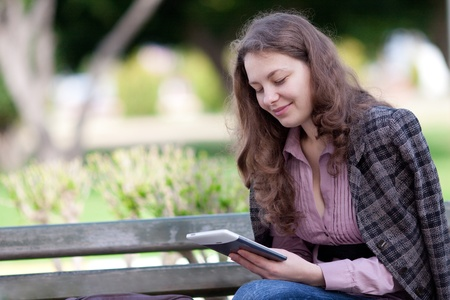 woman reading digital book at the park