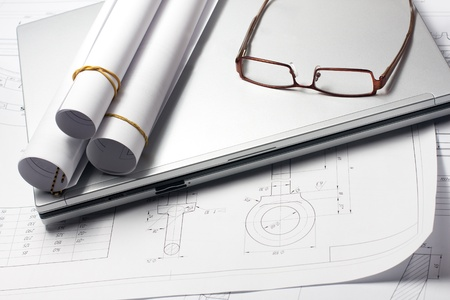 Rolled blueprints on the architects worckplace near laptop and glasses photo