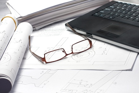 Laptop and glasses laying on opened blueprint